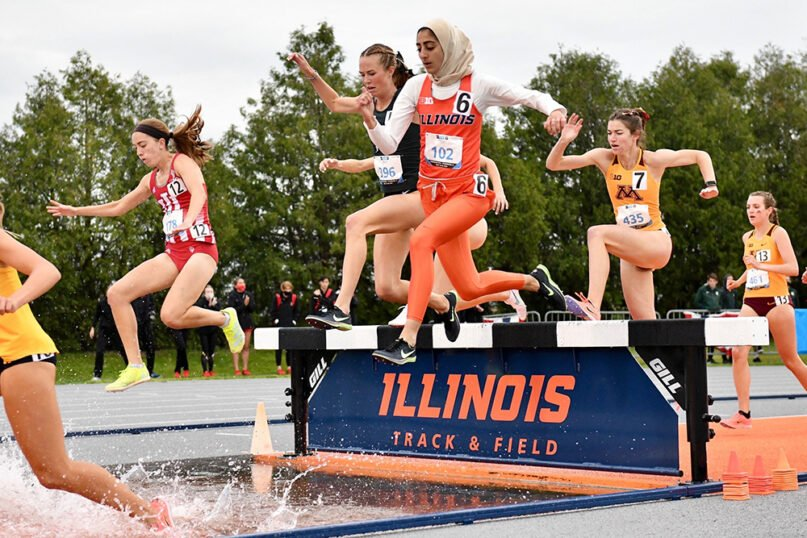 Ayah Aldadah, a runner with Illinois Track and Field, clears a hurdle and looks for her landing. Photo courtesy of UIUC Department of Athletics