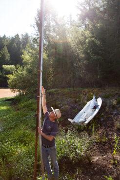 Farmer David Plescia of Green Valley Community Farm points to where the water level ought to be in an empty reservoir in Sebastopol, California. Photo © Kelsey Joy Murphey