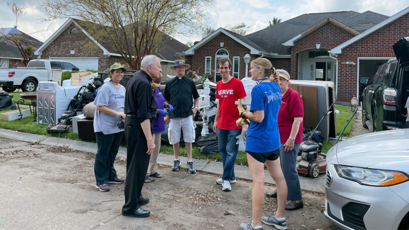 Archbishop Gregory Aymond, second from left, meets with volunteers from St. Luke the Evangelist Catholic Church and other churches who were helping with cleanup efforts in LaPlace, Louisiana, after Hurricane Ida. Photo courtesy of the Archdiocese of New Orleans