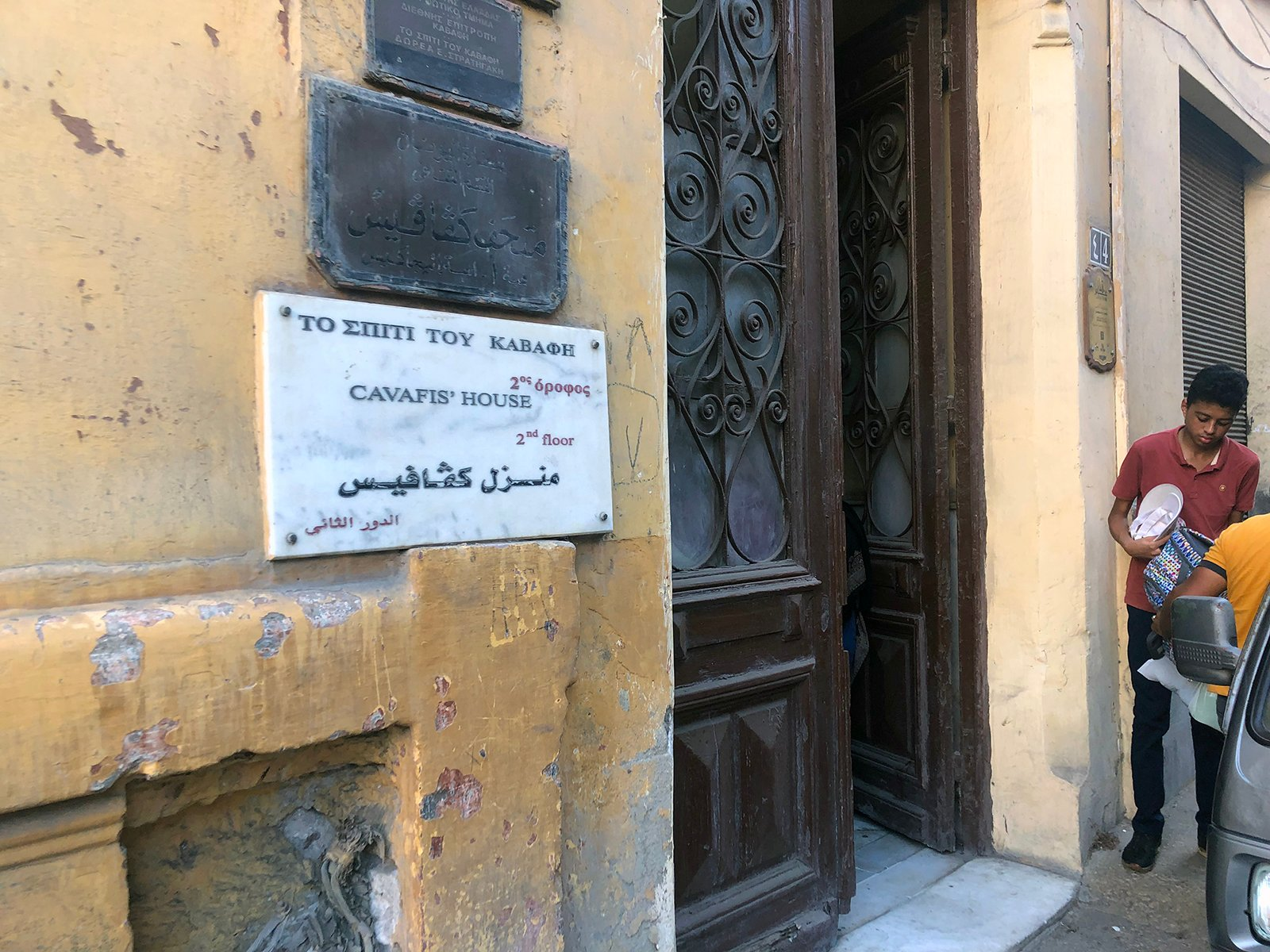 A marble sign in Arabic, English, and Greek notes the Constantine Cavafy apartment museum is on the second floor in Alexandria, Egypt. RNS photo by Joseph Hammond
