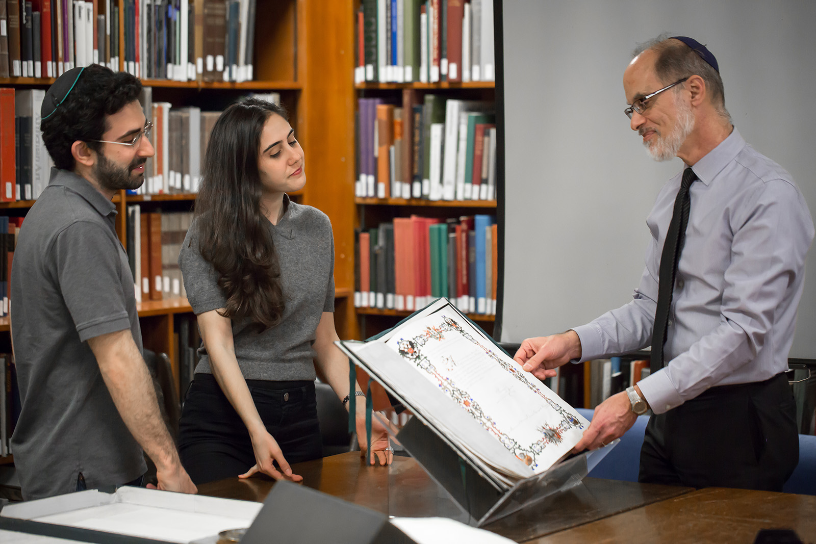 Librarian David Kraemer, right, shows manuscripts to students in 2017, when a number of rare materials were stored at the Metropolitan Museum of Art during construction of the new Jewish Theological Seminary library in New York. Photo by Jason Shaltz, courtesy of the Jewish Theological Seminary