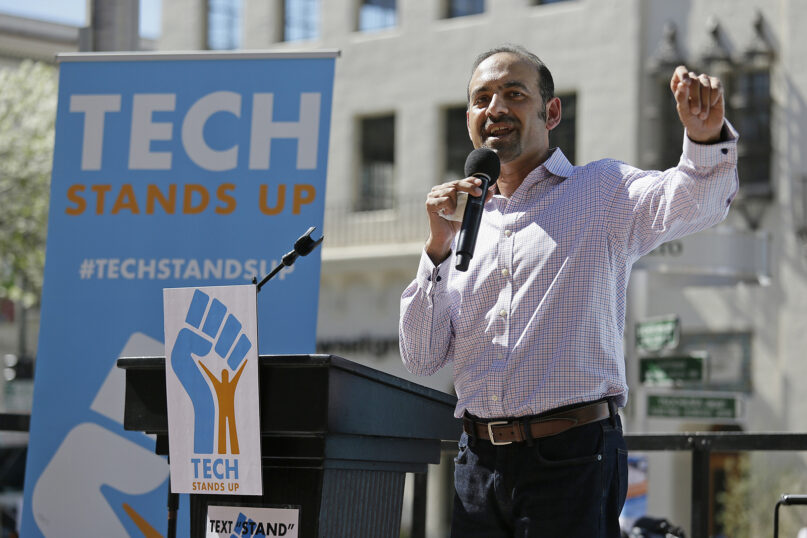 Dilawar Syed speaks during a Tech Stands Up rally on Pi Day, Tuesday, March 14, 2017, outside City Hall in Palo Alto, Calif. Subcontracted tech service workers and direct tech employees rallied together to call on their companies and CEOs to stand with their workers against injustice and hate. (AP Photo/Eric Risberg)