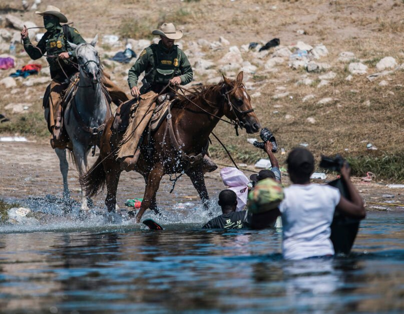 FILE - In this Sept. 19, 2021, file photo, U.S. Customs and Border Protection mounted officers attempt to contain migrants as they cross the Rio Grande from Ciudad Acuña, Mexico, into Del Rio, Texas. The Border Patrol's treatment of Haitian migrants, they say, is just the latest in a long history of discriminatory U.S. policies and of indignities faced by Black people, sparking new anger among Haitian Americans, Black immigrant advocates and civil rights leaders. (AP Photo/Felix Marquez, File)