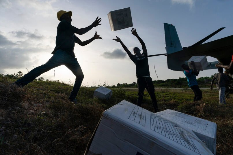 Haitian aid workers unload food from a VM-22 Osprey at Jeremie Airport, Aug. 28, 2021, in Jeremie, Haiti. A 7.2 magnitude earthquake on Aug. 22 caused heavy damage to the country. (AP Photo/Alex Brandon)