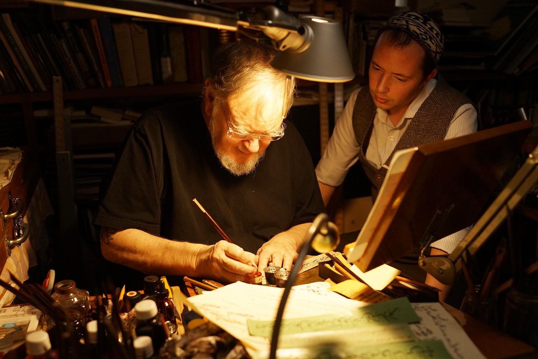 Josh Berer observes the work of Mohamed Zakariya at his work desk while learning Arabic calligraphy. Photo courtesy of Berer