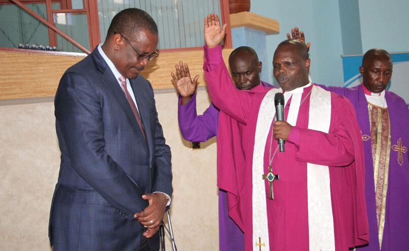 The Rev. Joseph Ntombura, with microphone, presiding bishop of the Methodist Church in Kenya, prays over former Nairobi Gov. Evans Kidero, left, in November 2015. RNS photo by Fredrick Nzwili