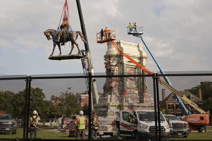 Crews remove one of the country's largest remaining monuments to the Confederacy, a towering statue of Confederate Gen. Robert E. Lee on Monument Avenue in Richmond, Virginia, on Sept. 8, 2021. (AP Photo/Steve Helber)