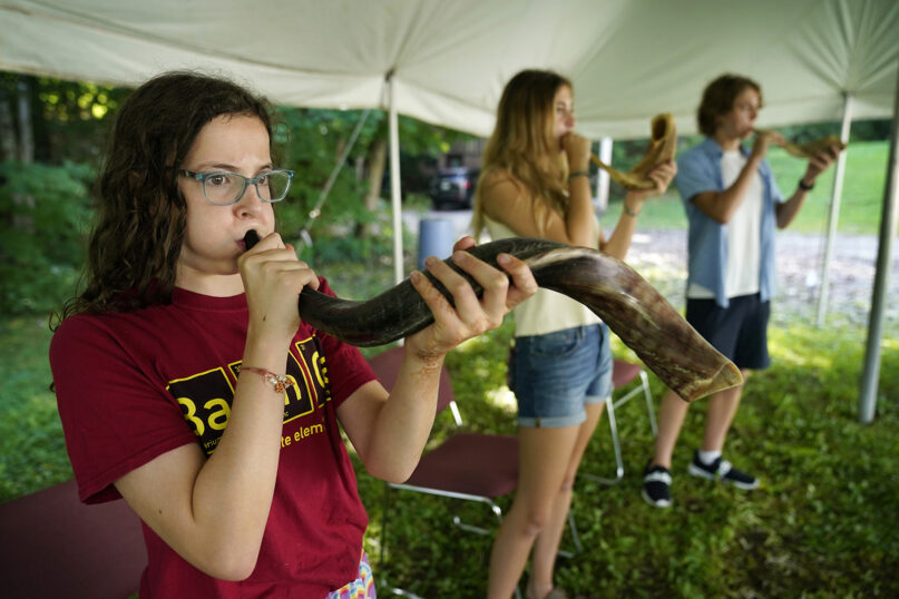 Robin Asch, left, Ava Katz, center, and Noah Katz practice playing their shofars, the ancient musical horns used in Judaism, under a tent set up outside Temple Beth El, Monday, Aug. 30, 2021, in Augusta, Maine. The recent COVID-19 upsurge is disrupting plans for full-fledged in-person services. (AP Photo/Robert F. Bukaty)