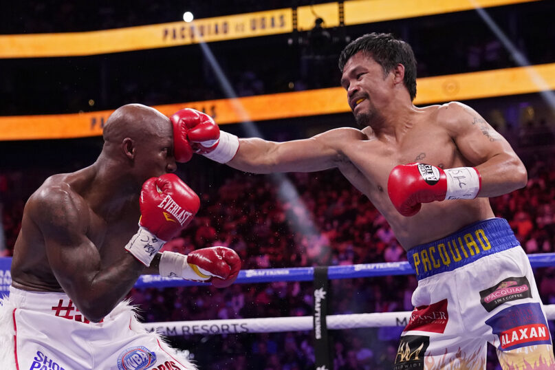 Manny Pacquiao, of the Philippines, right, hits Yordenis Ugas, of Cuba, in a welterweight championship boxing match Aug. 21, 2021, in Las Vegas. (AP Photo/John Locher)