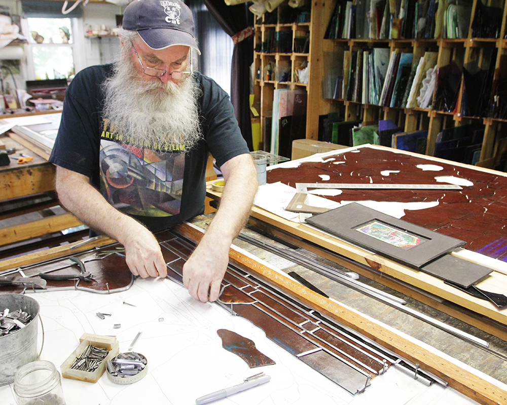 Stained glass artist Russell Joy glazes a window, inserting lead between pieces of glass, at his studio near Kansas City, Missouri, on Friday, Aug. 20, 2021. RNS photo by Kit Doyle