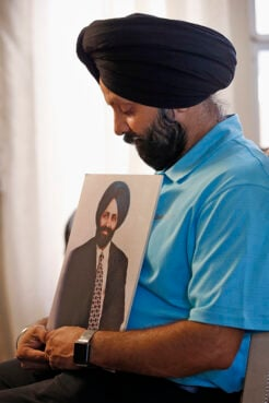 """FILE - In this Aug. 19, 2016 file photo Rana Singh Sodhi, holds a photograph of his murdered brother, Balbir Singh Sodhi, in Gilbert, Ariz. The Sikh American was killed at his Arizona gas station four days following the Sept. 11 attacks by a man who announced he was """"going to go out and shoot some towel-heads"""" and mistook him for an Arab Muslim. (AP Photo/Ross D. Franklin,File)"""