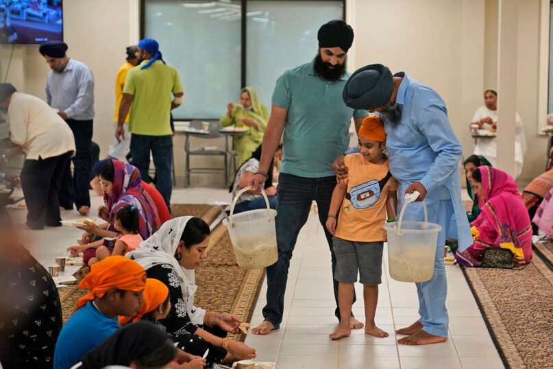 """Raghuvinder Singh, right, greets a child while helping to serve food after a Sikh worship service at a gurdwara in Glen Rock, New Jersey, on Aug. 15, 2021. Baba Punjab Singh, a Sikh priest visiting from India, was shot in the head by a white supremacist Army veteran in Wisconsin in 2012, and left partially paralyzed. He died from his wounds in 2020. Over seven years, the priest's son, Raghuvinder Singh, split his time between caring for his father in Oak Creek and working in Glen Rock, New Jersey, as assistant priest at a gurdwara there. Raghuvinder said the greatest lesson his father taught him was how to embody """"chardi kala,"""" which calls for steadfast optimism in the face of oppression. (AP Photo/Seth Wenig)"""