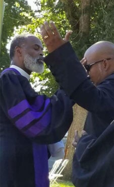 AME Zion Bishop Staccato Powell, left, prays for the Rev. Ed Prothro-Harris. Photo courtesy of Ed Prothro-Harris