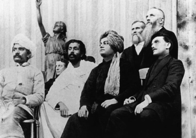Swami Vivekananda, seated second from right, at the Parliament of the World's Religions, Sept. 11, 1893, in Chicago.  Also on stage are Virchand Gandhi, seated from left, Hewivitarne Dharmapala, Vivekananda and possibly G. Bonet Maury. Photo courtesy of Creative Commons