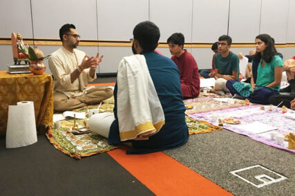 Vineet Chander sits with a group of students and explains puja. Photo courtesy of Chander