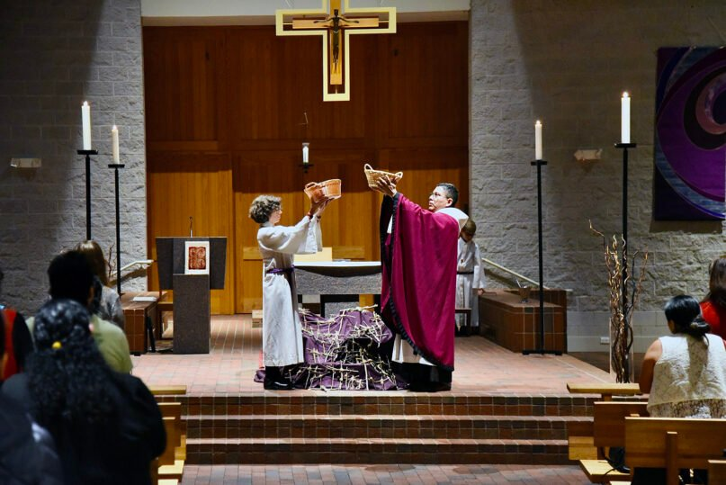 Casey Stanton, left, and the Rev. Mario Gomez raise up the prayers people have written down at the culmination of a parish retreat at Immaculate Conception Catholic Church in Durham, North Carolina, in March 2020. Photo by John Witchger