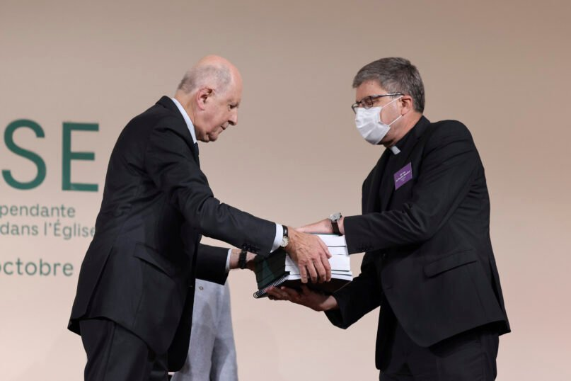 Commission president Jean-Marc Sauve, left, hands copies of the report to Catholic Bishop Eric de Moulins-Beaufort, president of the Bishops' Conference of France (CEF), during the publishing of a report by an independant commission into sexual abuse by church officials (Ciase), Tuesday, Oct. 5, 2021, in Paris. A major French report released Tuesday found that an estimated 330,000 children were victims of sex abuse within France's Catholic Church over the past 70 years, in France's first major reckoning with the devastating phenomenon. (Thomas Coex, Pool via AP)
