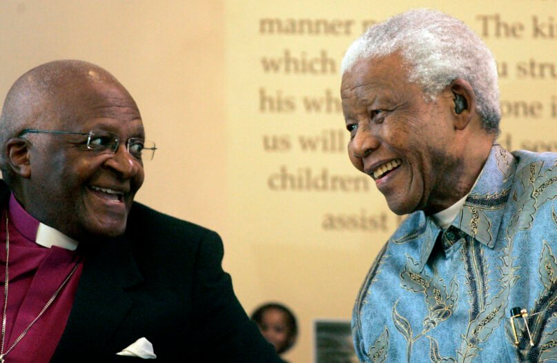 FILE — In this March 12, 2008 file photo, Former South African President Nelson Mandela, right, reacts with Archbishop Desmond Tutu, left, in Johannesburg, South Africa, As South Africa's anti-apartheid icon Archbishop Desmond Tutu turns 90, recent racist graffiti on a portrait of the Nobel winner highlights the continuing relevance of his work for equality. (AP Photo/Themba Hadebe/File)