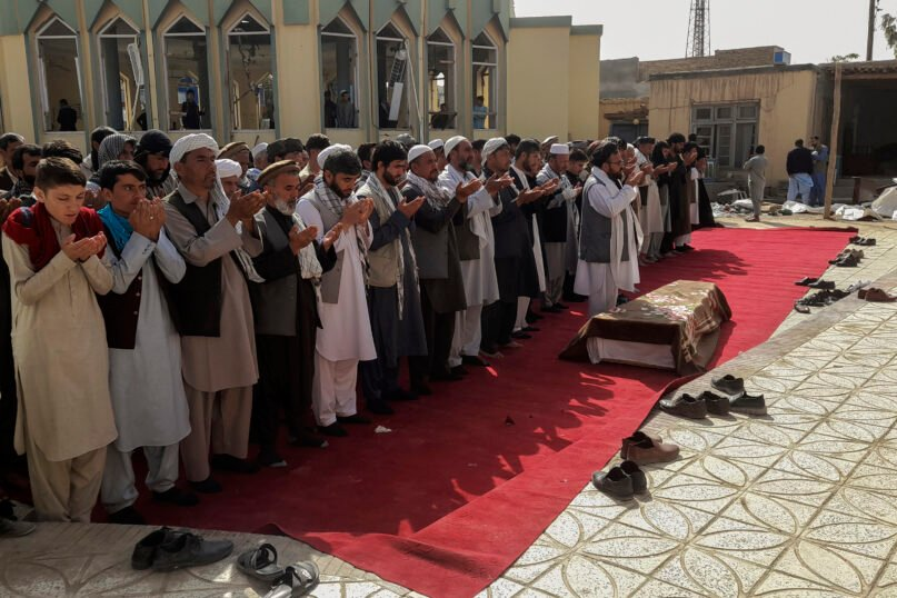 Relatives and residents pray during a funeral ceremony for victims of a suicide attack at the Gozar-e-Sayed Abad Mosque in Kunduz, northern Afghanistan, Saturday, Oct. 9, 2021. The mosque was packed with Shiite Muslim worshippers when an Islamic State suicide bomber attacked during Friday prayers, killing dozens in the latest security challenge to the Taliban as they transition from insurgency to governance. (AP Photo/Abdullah Sahil)