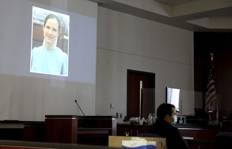 Mark Gooch, 22, sits below an image of Sasha Krause shown on a screen during his trial at the Coconino County Superior Court in Flagstaff, Arizona, on Sept. 24, 2021. Gooch was charged with first-degree murder in Krause's death in early 2020. (Jake Bacon/Arizona Daily Sun via AP)