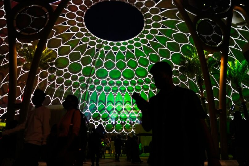 People walk past the Al Wasl Dome as it is lit at night at Expo 2020 in Dubai, United Arab Emirates, Friday, Oct. 1, 2021. After eight years of planning and billions of dollars in spending, the Middle East's first ever World Fair opened on Friday in Dubai, with hopes the months-long extravaganza draws both visitors and global attention to this desert-turned-dreamscape. (AP Photo/Jon Gambrell)