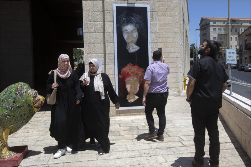In this July 1, 2021, photo provided by the The Lonka Project, people look at the defaced portrait of Holocaust survivor Peggy Parnass, outside Jerusalem City Hall, where it is on display as part of an exhibit that tells the stories of 400 survivors of the Nazi atrocities during World War II in The Lonka Project exhibition in Safra Square in Jerusalem. Israel is having a difficult time keeping images of women in public from being defaced. Billboards showing women -- whether they are soccer players, musicians or young girls -- have been repeatedly defaced and torn down by religious extremists in Jerusalem and other cities.  (Jim Hollander/The Lonka Project via AP)