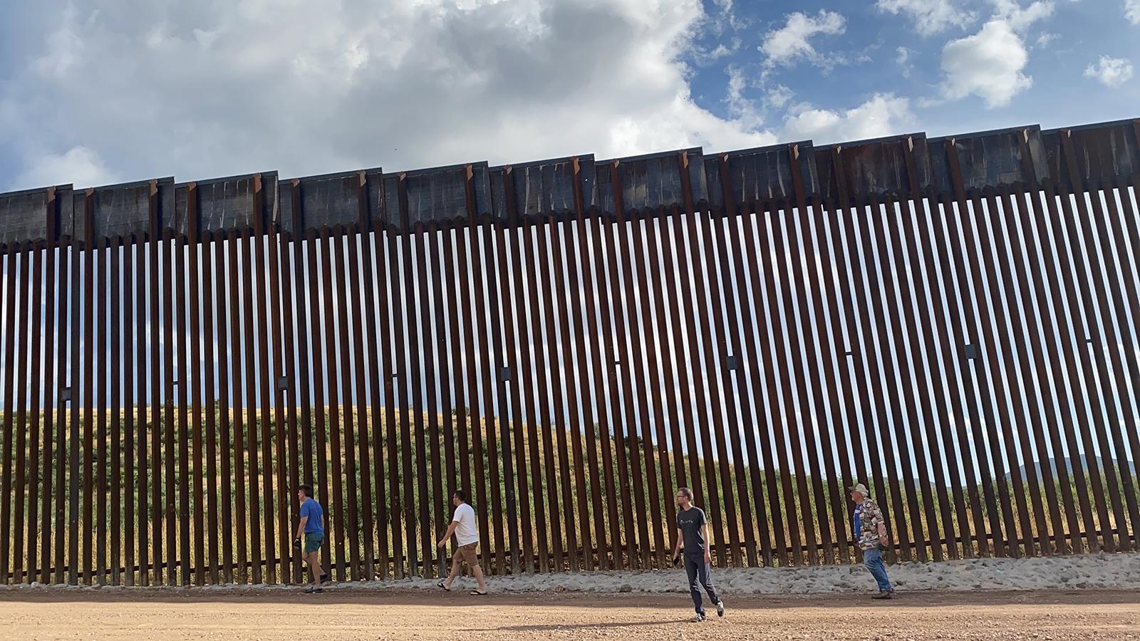 Participantes de We People Ride caminando a fines de septiembre de 2021 en una sección de la valla fronteriza en la frontera entre Estados Unidos y México.  Votar por el bien común