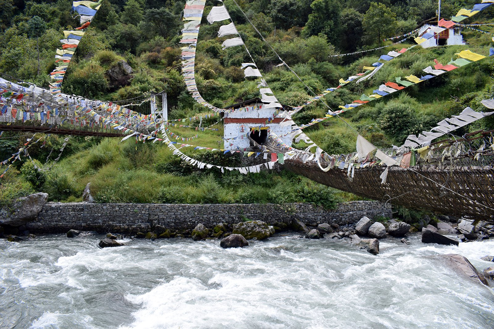 Prayer flags flap on and around the 600-year-old Chagzam Bridge, right, which was built by a disciple of the First Dalai Lama. The famous bridge spans the Tawang River in Arunachal Pradesh, India. RNS photo by Priyadarshini Sen