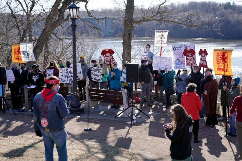 Protesters gather at an overlook along the Mississippi River in St. Paul, Minn., Thursday, March 11, 2021, to call on President Biden to stop the tar sands Line 3 pipeline that Enbridge is currently constructing in northern Minnesota. (AP Photo/Jim Mone)