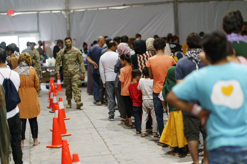 Afghan refugees line up for food in a dining hall at Fort Bliss' Doña Ana Village, in New Mexico, where they are being housed, Friday, Sept. 10, 2021. (AP Photo/David Goldman)