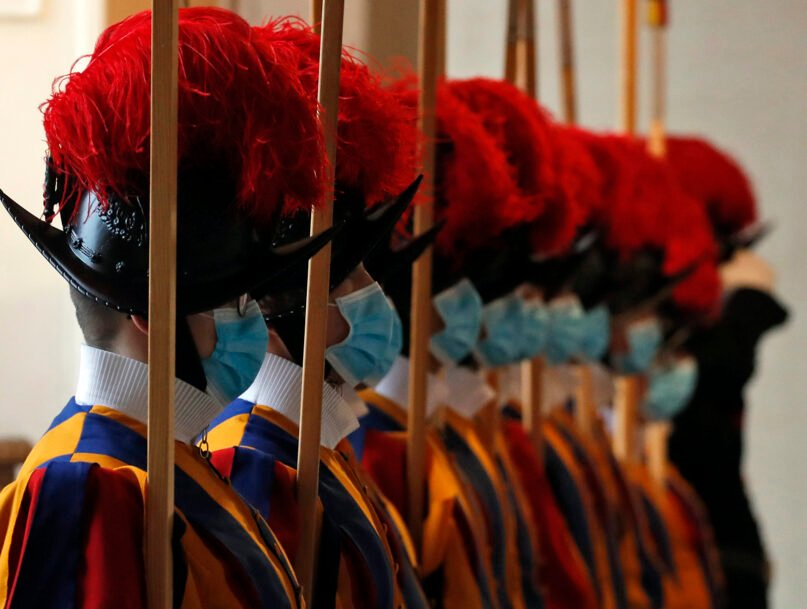 """FILE - In this Saturday, Oct. 24, 2020 file photo, Vatican Swiss Guards wear masks to curb the spread of COVID-19 as they stand at attention at the Vatican. Three Vatican Swiss Guards have refused to be vaccinated against COVID-19 upon Holy See orders and have left the storied corps to return to Switzerland. A Swiss Guard official, Lt. Urs Breitenmoser, told The Associated Press on Sunday that all Swiss Guards were asked to be vaccinated """"to protect their health and that of the others they come into contact as part of their service."""" (AP Photo/Alessandra Tarantino, File)"""